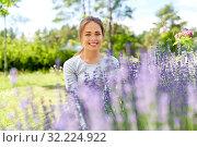 Купить «young woman and lavender flowers at summer garden», фото № 32224922, снято 12 июля 2019 г. (c) Syda Productions / Фотобанк Лори