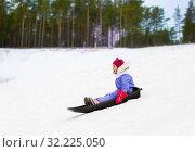 Купить «happy little girl sliding down on sled in winter», фото № 32225050, снято 10 февраля 2018 г. (c) Syda Productions / Фотобанк Лори