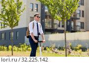 Купить «businessman with backpack riding electric scooter», фото № 32225142, снято 1 августа 2019 г. (c) Syda Productions / Фотобанк Лори
