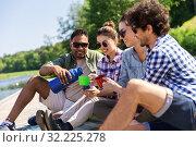Купить «happy friends drinking tea from thermos in summer», фото № 32225278, снято 15 июня 2019 г. (c) Syda Productions / Фотобанк Лори