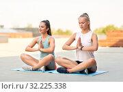 Купить «women doing yoga and meditating in lotus pose», фото № 32225338, снято 28 июля 2019 г. (c) Syda Productions / Фотобанк Лори
