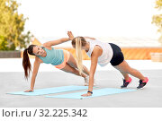Купить «women making high five in side plank on sport mats», фото № 32225342, снято 28 июля 2019 г. (c) Syda Productions / Фотобанк Лори
