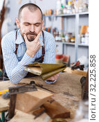 Купить «Annoyed workman in repair furniture workshop», фото № 32225858, снято 19 ноября 2018 г. (c) Яков Филимонов / Фотобанк Лори