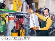 Ordinary guy deciding on best garden sprayer. Стоковое фото, фотограф Яков Филимонов / Фотобанк Лори
