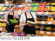 Купить «Young female seller with half of melon and man on background having box of green beans on the supermarket», фото № 32225978, снято 27 апреля 2019 г. (c) Яков Филимонов / Фотобанк Лори