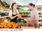 Купить «Young woman selling fresh oranges to man», фото № 32225994, снято 27 апреля 2019 г. (c) Яков Филимонов / Фотобанк Лори