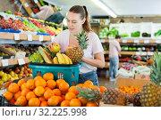 Купить «Woman standing with full shopping cart during shopping in fruit store», фото № 32225998, снято 27 апреля 2019 г. (c) Яков Филимонов / Фотобанк Лори