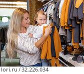 Купить «Woman and daughter buying kids clothes», фото № 32226034, снято 9 октября 2018 г. (c) Яков Филимонов / Фотобанк Лори