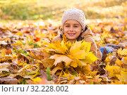 Купить «Осенний портрет. Счастивая девочка с букетом из кленовых листев лежит на траве в осеннем парке», фото № 32228002, снято 14 октября 2018 г. (c) Лариса Капусткина / Фотобанк Лори