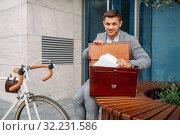 Businessman bicyclist puts document into briefcase. Стоковое фото, фотограф Tryapitsyn Sergiy / Фотобанк Лори