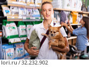 Portrait of a boy with dog during selecting dry food in petshop, woman on background. Стоковое фото, фотограф Яков Филимонов / Фотобанк Лори