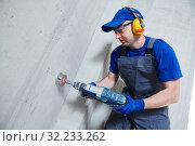 Купить «boring hole for electric outlet by power tool drill.», фото № 32233262, снято 28 мая 2018 г. (c) Дмитрий Калиновский / Фотобанк Лори
