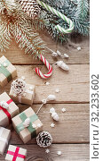 Купить «Christmas green branch and gifts on wooden background», фото № 32233602, снято 15 октября 2018 г. (c) Майя Крученкова / Фотобанк Лори