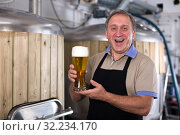 Adult brewer is standing with golden beer in glass. Стоковое фото, фотограф Яков Филимонов / Фотобанк Лори