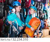 Купить «Smiling couple in shop chooses backpacks», фото № 32234310, снято 25 октября 2017 г. (c) Яков Филимонов / Фотобанк Лори