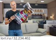 Купить «Client choosing upholstery fabric from catalog with samples», фото № 32234402, снято 29 октября 2018 г. (c) Яков Филимонов / Фотобанк Лори
