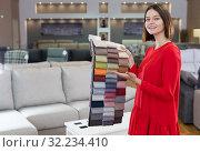 Купить «Shop assistant demonstrating samples of upholstery fabric», фото № 32234410, снято 29 октября 2018 г. (c) Яков Филимонов / Фотобанк Лори
