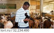 Купить «Farmworker with goatlings», фото № 32234490, снято 15 декабря 2018 г. (c) Яков Филимонов / Фотобанк Лори