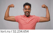 Купить «indian man showing biceps over grey background», видеоролик № 32234654, снято 12 сентября 2019 г. (c) Syda Productions / Фотобанк Лори
