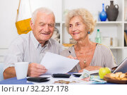 Happy senior spouses with bills and laptop. Стоковое фото, фотограф Яков Филимонов / Фотобанк Лори