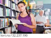 Young woman customer is looking new novel. Стоковое фото, фотограф Яков Филимонов / Фотобанк Лори