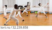 Купить «adults and teenagers athletes at fencing workout», фото № 32239858, снято 30 мая 2018 г. (c) Яков Филимонов / Фотобанк Лори