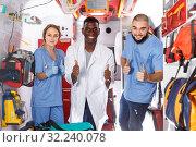 Купить «Portrait of three cheerful paramedicals posing in ambulance car», фото № 32240078, снято 30 ноября 2018 г. (c) Яков Филимонов / Фотобанк Лори