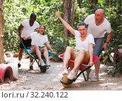 Купить «Competitions in amusement park - who will quickly bring girl in the garden wheelbarrow», фото № 32240122, снято 19 октября 2019 г. (c) Яков Филимонов / Фотобанк Лори