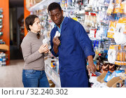 Купить «Competent seller consulting young woman about purchase of supplies for household works in store», фото № 32240302, снято 21 января 2019 г. (c) Яков Филимонов / Фотобанк Лори