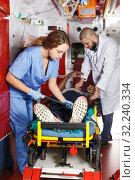 Купить «Ambulance team laying patient on stretcher», фото № 32240334, снято 30 ноября 2018 г. (c) Яков Филимонов / Фотобанк Лори