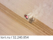 Tractor cultivates arable land with a disk harrow on an autumn day, view from a drone. Стоковое фото, фотограф Mikhail Starodubov / Фотобанк Лори