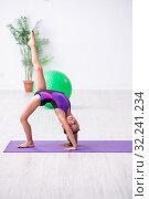 Купить «Little girl gymnast doing exercises indoors», фото № 32241234, снято 16 июля 2019 г. (c) Elnur / Фотобанк Лори