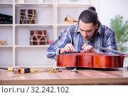 Купить «Young handsome repairman repairing cello», фото № 32242102, снято 4 апреля 2019 г. (c) Elnur / Фотобанк Лори