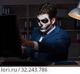 Купить «Businessman with scary face mask working late in office», фото № 32243786, снято 9 ноября 2017 г. (c) Elnur / Фотобанк Лори