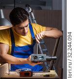 Купить «Worker working in repair workshop in woodworking concept», фото № 32244094, снято 11 августа 2017 г. (c) Elnur / Фотобанк Лори
