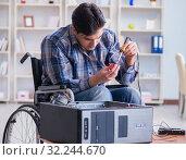 Купить «Disabled man on wheelchair repairing computer», фото № 32244670, снято 20 апреля 2017 г. (c) Elnur / Фотобанк Лори
