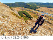 Купить «Man Tourist with a backpack is on top of the High Rock Mountain below, the Zilyim River flows against the background of the Ural Mountains. Autumn sunny day.», фото № 32245866, снято 30 августа 2016 г. (c) Акиньшин Владимир / Фотобанк Лори