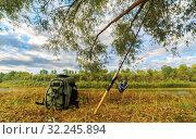 Купить «Spinning and backpack lying on the river bank near the tree, the main fishing accessories.», фото № 32245894, снято 31 августа 2016 г. (c) Акиньшин Владимир / Фотобанк Лори
