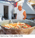 Купить «Russia, Sol-Iletsk, August 2016: a cook at a street cafe is cooking pilaf in a large cauldron. Summer sunny day.», фото № 32246570, снято 8 августа 2016 г. (c) Акиньшин Владимир / Фотобанк Лори