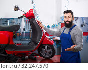 attractive man worker displaying his workplace in motorcycle workshop. Стоковое фото, фотограф Яков Филимонов / Фотобанк Лори