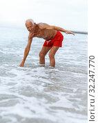 Купить «Portrait of jolly man checks water temperature», фото № 32247770, снято 16 июня 2018 г. (c) Яков Филимонов / Фотобанк Лори