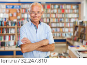 Купить «Portrait of smiling senior man in interior of modern bookstore», фото № 32247810, снято 11 июня 2018 г. (c) Яков Филимонов / Фотобанк Лори