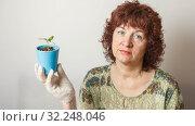 Купить «A female gardener shows a pot with sprouts after a pick.», фото № 32248046, снято 3 апреля 2016 г. (c) Акиньшин Владимир / Фотобанк Лори