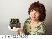 Купить «A female gardener shows a pot with sprouts after a pick.», фото № 32248050, снято 3 апреля 2016 г. (c) Акиньшин Владимир / Фотобанк Лори
