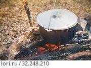 Купить «Closed cauldron boiling on a campfire», фото № 32248210, снято 14 июля 2019 г. (c) EugeneSergeev / Фотобанк Лори