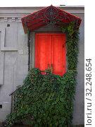 Купить «Старая красная деревянная дверь с цветущими лианами на фоне серой винтажной стены. Цветочное декорирование входа в дом.», фото № 32248654, снято 1 октября 2019 г. (c) Дорощенко Элла / Фотобанк Лори