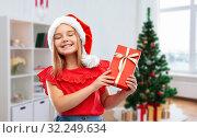 Купить «girl in santa hat with christmas gift at home», фото № 32249634, снято 9 марта 2019 г. (c) Syda Productions / Фотобанк Лори