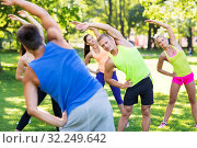 group of happy people exercising at summer park. Стоковое фото, фотограф Syda Productions / Фотобанк Лори
