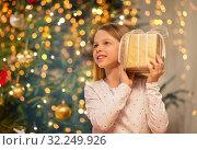 Купить «smiling girl with christmas gift at home», фото № 32249926, снято 22 декабря 2017 г. (c) Syda Productions / Фотобанк Лори