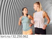 Купить «women or female friends with earphones running», фото № 32250062, снято 28 июля 2019 г. (c) Syda Productions / Фотобанк Лори